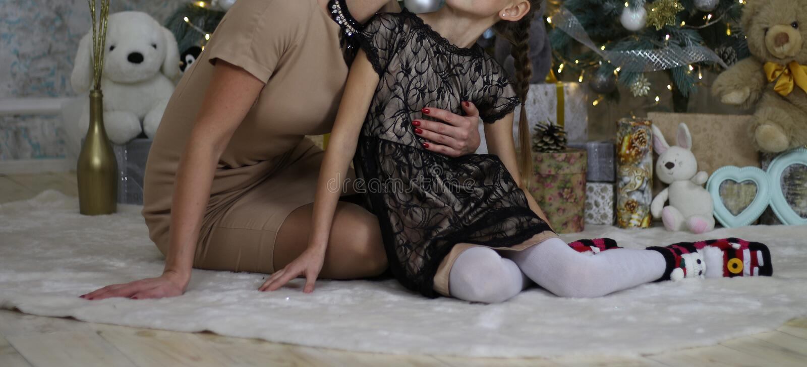 Mother hugs and kisses daughter on the background of Christmas tree, gifts and toys, sitting on the floor, New Year Eve, happin royalty free stock photo