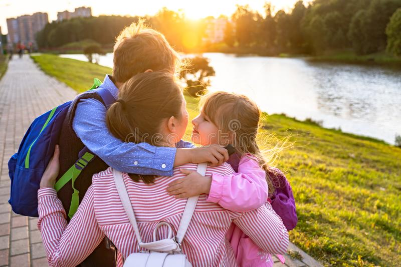 Mother hugs son and daughter sends children to school stock photos