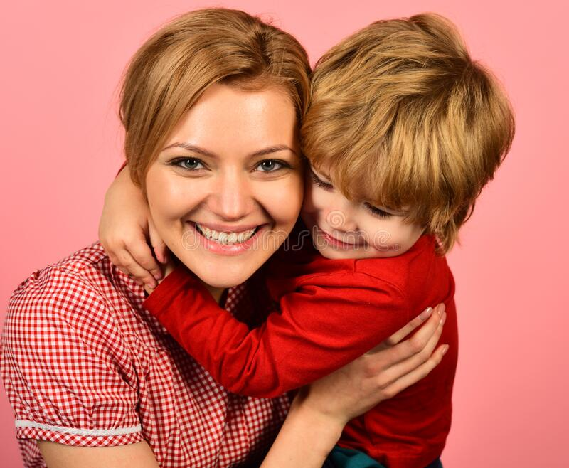 Mother hugs son on pink background. Family happiness concept stock photos