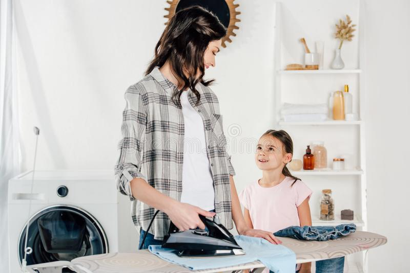 mother ironing and looking to daughter standing near stock photography