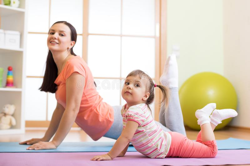 Mother and kid daughter doing yoga exercises on floor in room at home. Family having fun indoors with fitness. Mother and kid daughter doing yoga exercises on royalty free stock photo