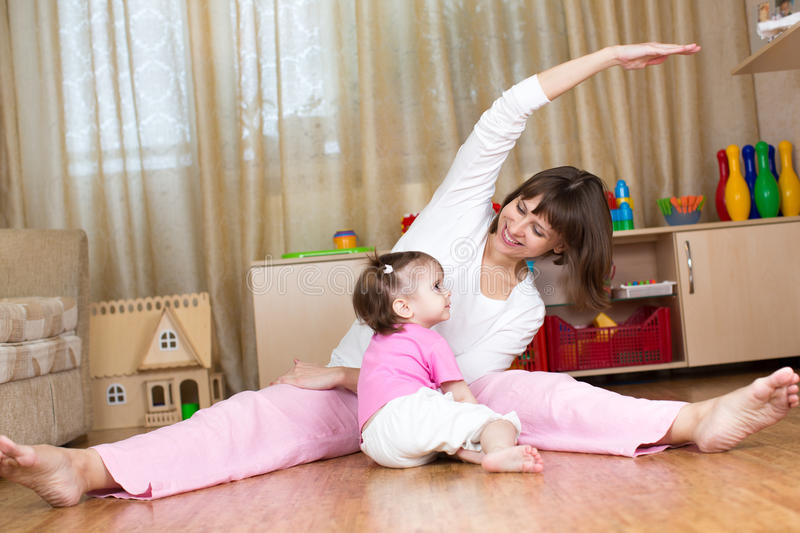 Mother and kid doing gymnastic at home stock images