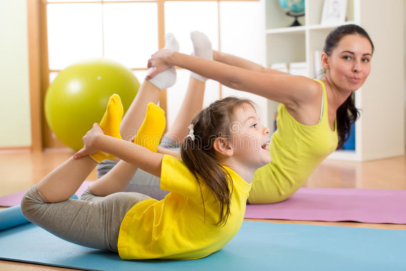 Mother and kid doing yoga exercises on rug at home. Mother and kid daughter doing yoga exercises on rug at home stock photography
