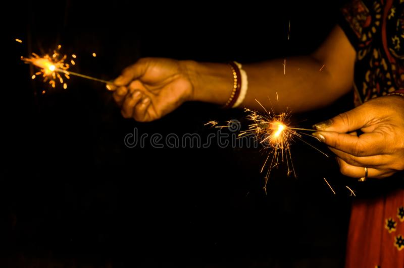Mother and kid holding sparklers on black background royalty free stock image