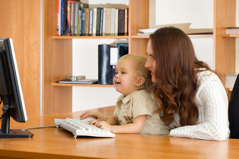 Mother with kid looking monitor stock photos