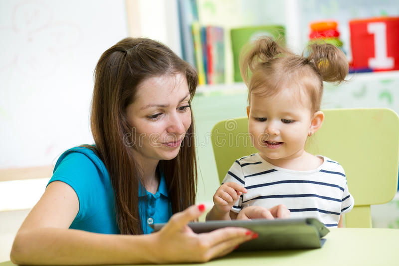 Mother and kid are looking to play and read tablet computer. At home royalty free stock images
