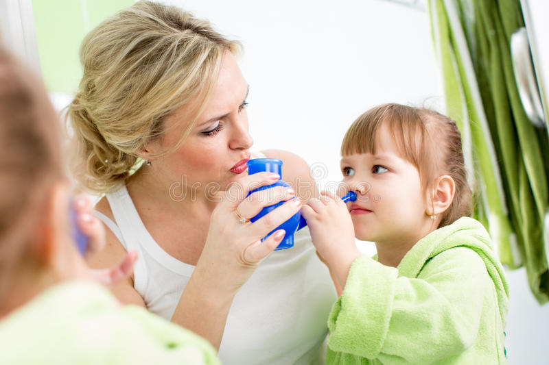 Mother and kid with neti pot for nasal irrigation stock image