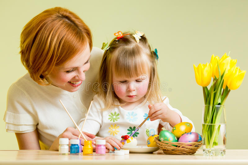 Mother And Kid Painting Easter Eggs Stock Photos