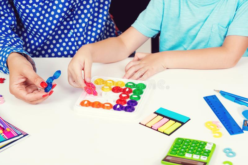 Mother and kid plays logic game at table. Logical thinking training. Modern logic games. Workplace table with calculator, pens and. Notebooks. Education and royalty free stock photography