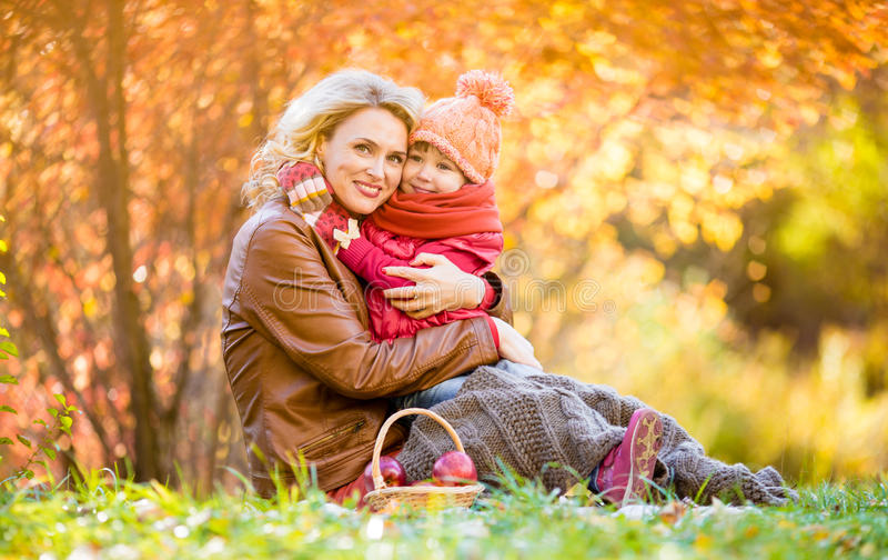 Mother and kid sitting and hugging together in autumn park. stock photography