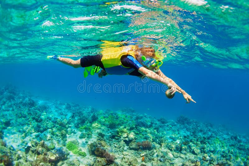 Mother, kid in snorkeling mask dive underwater with tropical fishes. Happy family - mother, kid in snorkeling mask dive underwater, explore tropical fishes in stock photos