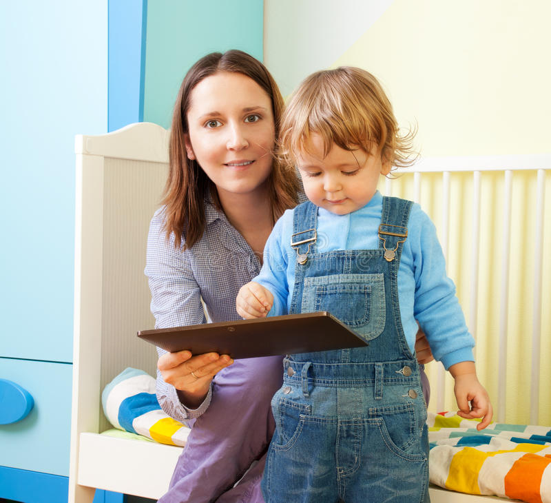 Mother with kid and tablet computer. Happy mother with kid and tablet computer in nursery room royalty free stock photo