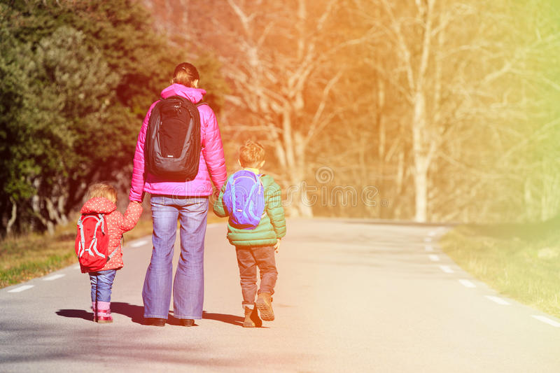 Mother and kids with backpacks walking on the road royalty free stock photo