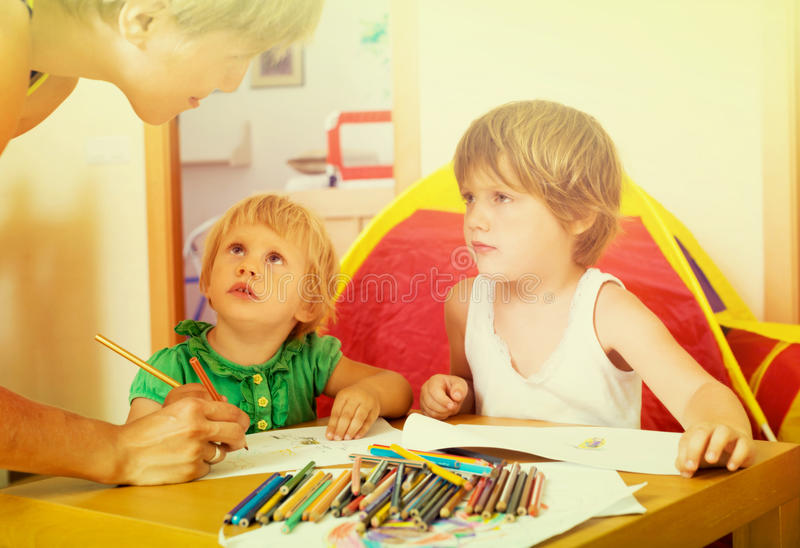 Mother and kids drawing with pencils. Happy mother and two little girls sketching on paper in home interior stock photos