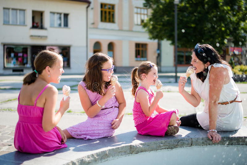 Mother with kids eating ice-cream outdoors. Happy family eating ice-cream. Mother with three daughters royalty free stock photography