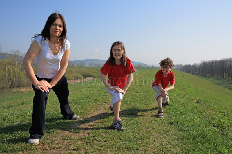 Mother with kids exercising. Active family - mother with kids exercising stock image