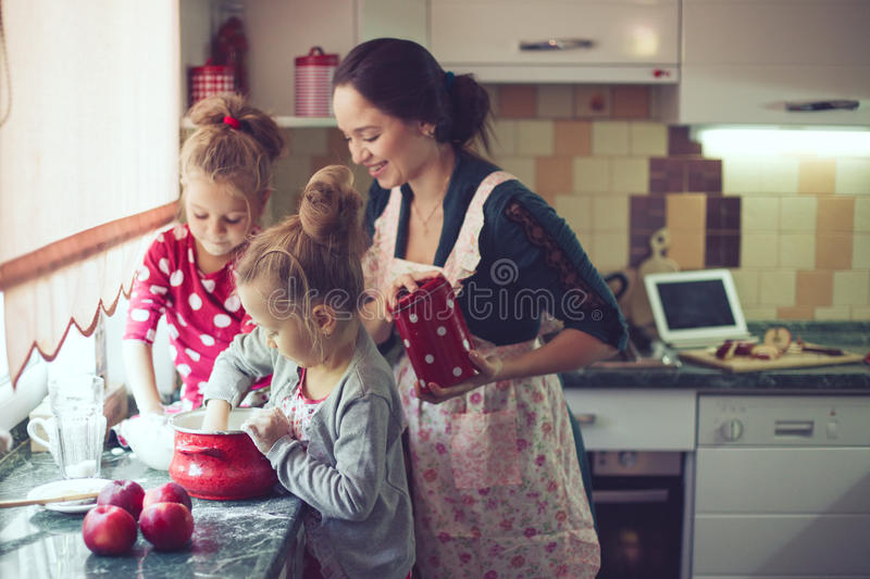 Mother with kids at the kitchen. Mother with her 5 years old kids cooking holiday pie in the kitchen, casual lifestyle photo series in real life interior royalty free stock photo