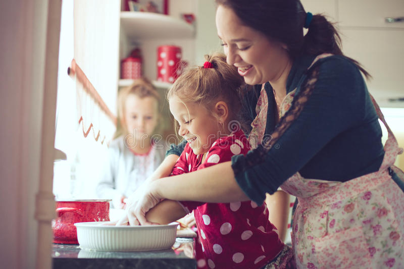 Mother with kids at the kitchen. Mother with her 5 years old kids cooking holiday pie in the kitchen, casual lifestyle photo series in real life interior royalty free stock photography