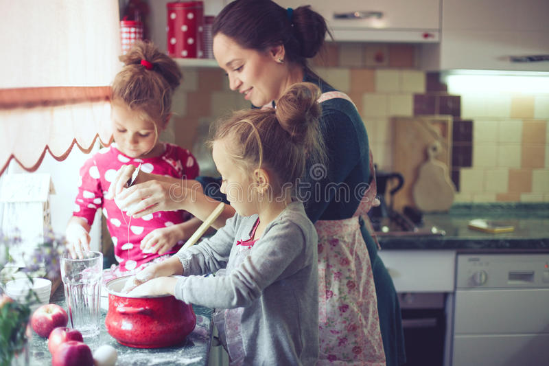Mother with kids at the kitchen stock images