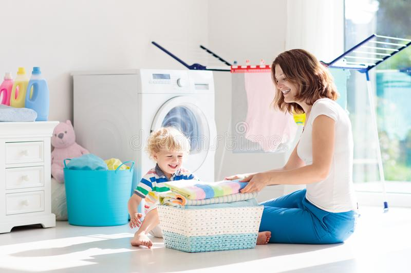 Family in laundry room with washing machine royalty free stock photos