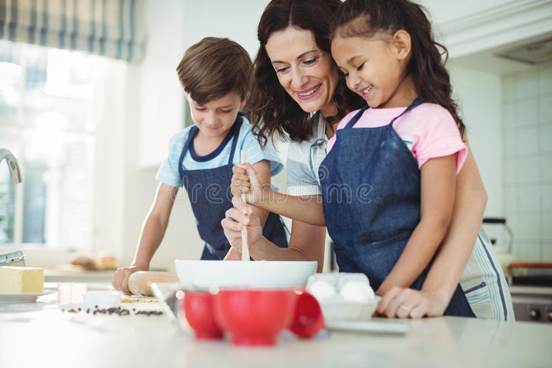 Mother and kids mixing the dough while preparing cookies royalty free stock photography