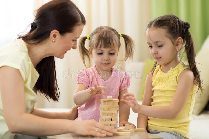 Mother with kids play board game in living room. Family spending time together at home royalty free stock image