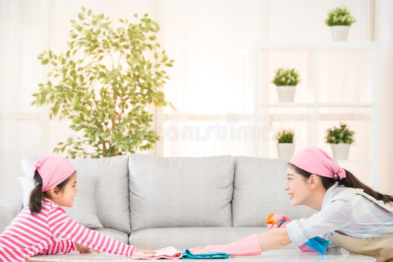 Mother and kids playing and cleaning. Happy asian chinese mother and kids playing and cleaning living room together at home face to each other. housework and royalty free stock photo