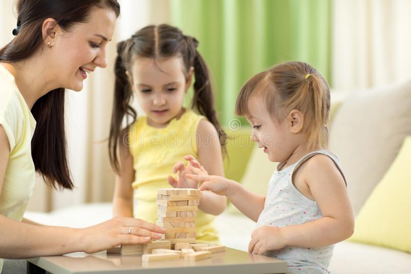Mother with kids play jenga game in living room stock image