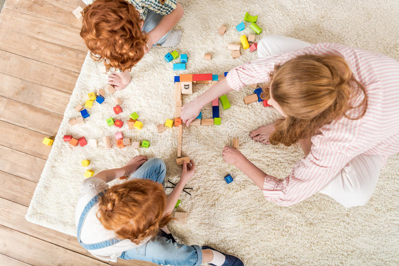 Mother and kids playing with toys, family fun at home concept. Overhead view of mother and kids playing with toys, family fun at home concept stock image