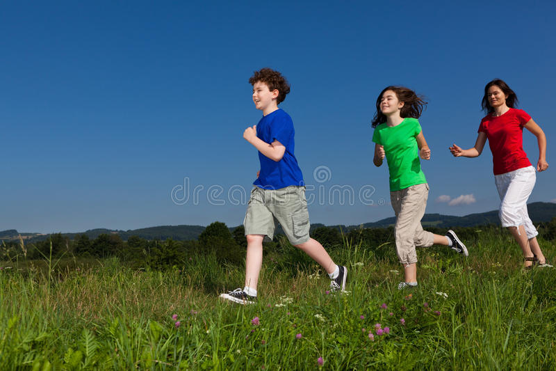 Mother with kids running. Active family - mother with kids running on green meadow royalty free stock photo