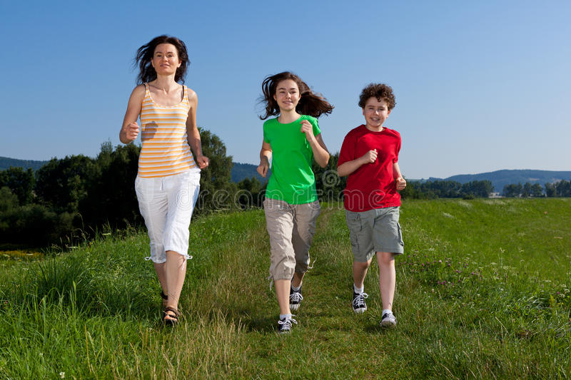 Mother with kids running. Active family - mother with kids running on green meadow stock photography