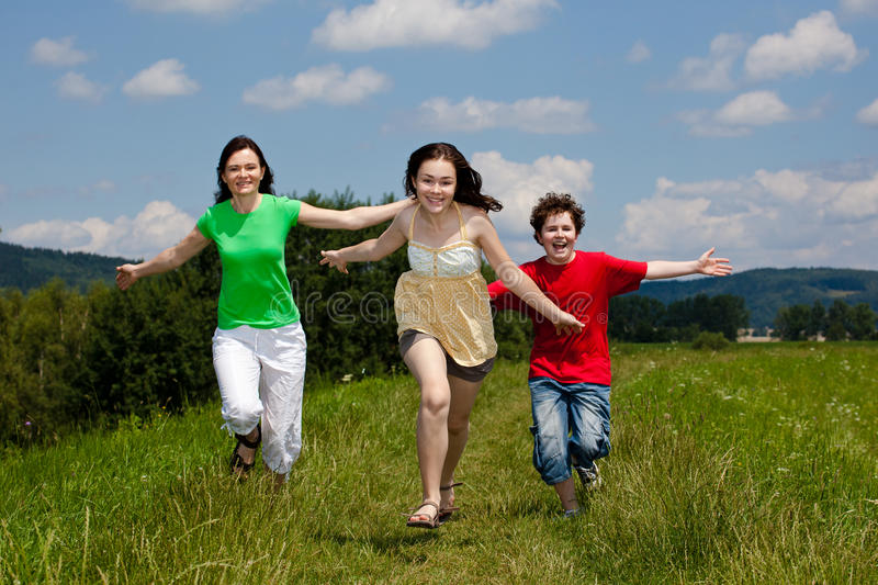 Mother with kids running outdoor. Active family - mother with kids running on green meadow royalty free stock image