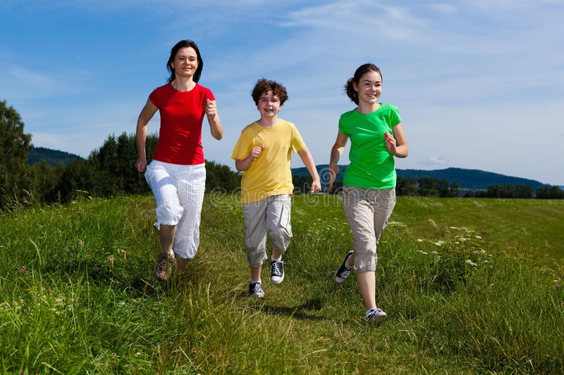 Mother with kids running outdoor. Active family - mother with kids running on green meadow stock photography