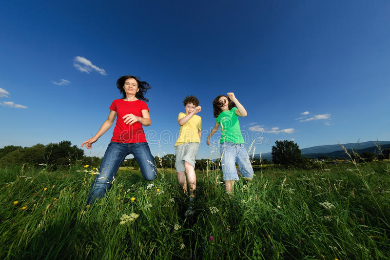 Mother with kids running outdoor. Active family - mother with kids running, jumping on green meadow stock image