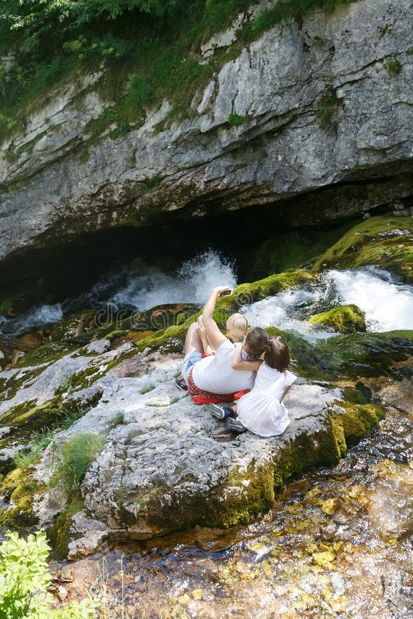 Mother with kids taking a selfie, sitting on a rock by a mountain stream on a family trip stock image