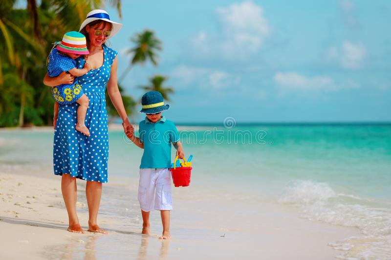 Mother with kids walk on beach, family vacation stock photos