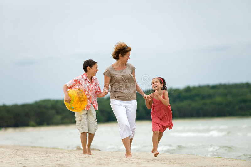 Mother and kids walking on the beach royalty free stock photo