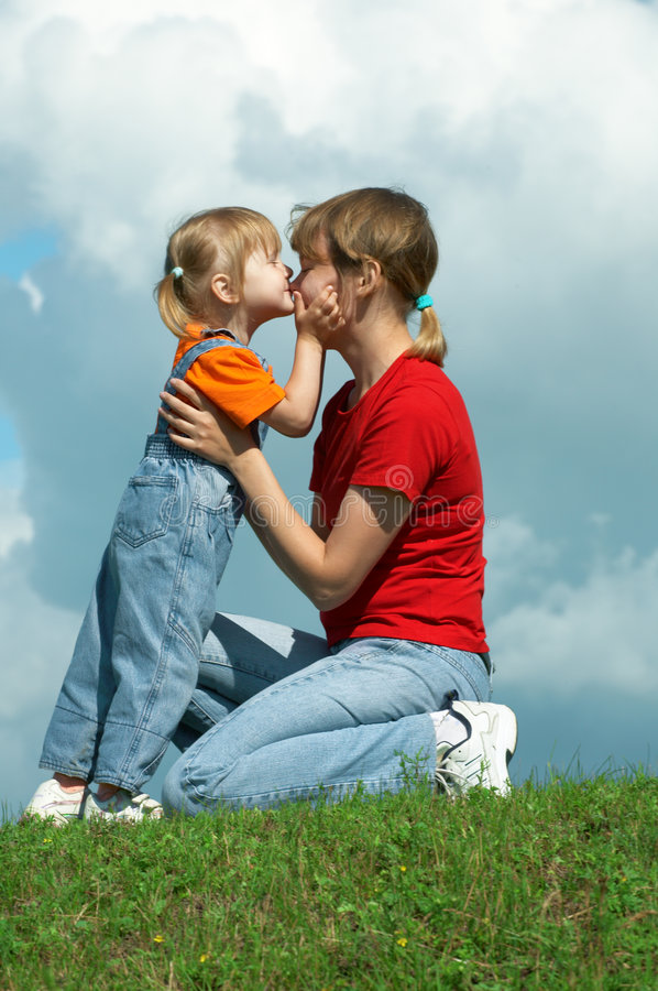 Mother kiss little daughter on green grass royalty free stock photos