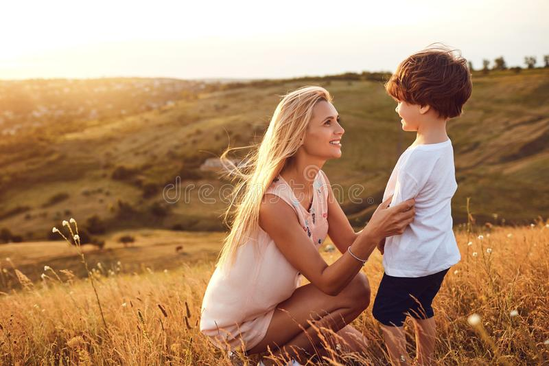 A mother kisses her son in nature. royalty free stock photo