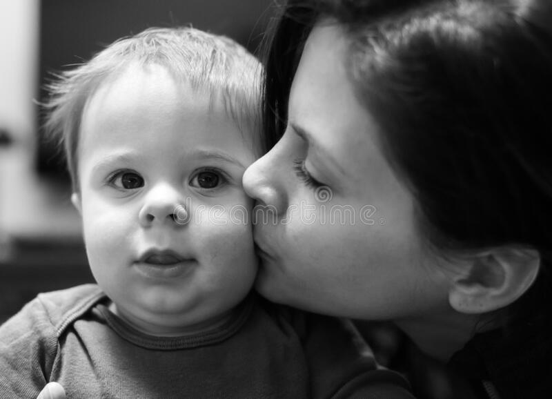 Mother kissing a baby boy stock photo