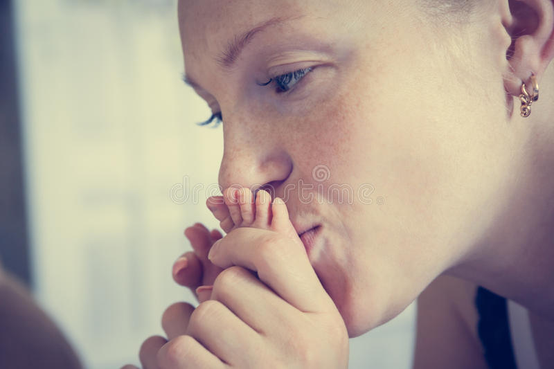 Mother kissing her baby feet symbolizing tenderness and care stock image