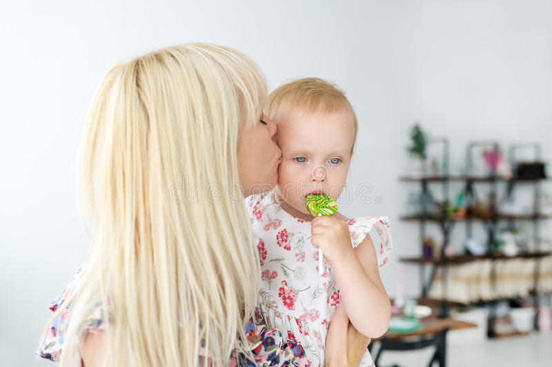 Mother kissing her baby`s. Mother holding infant`s. Portrait of a mother with baby at home. Mother kissing her baby`s with lollipop. Mother holding infant`s stock image