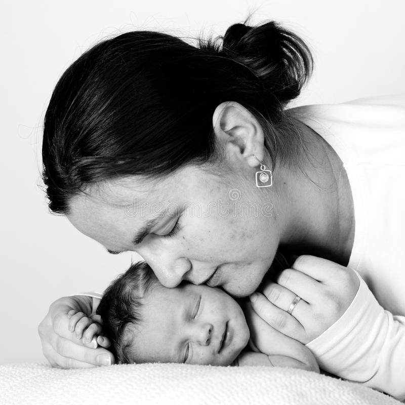 Mother kissing her child stock photography