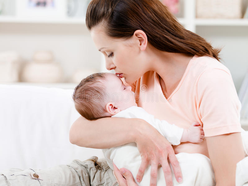 Mother kissing her sleeping baby royalty free stock photography