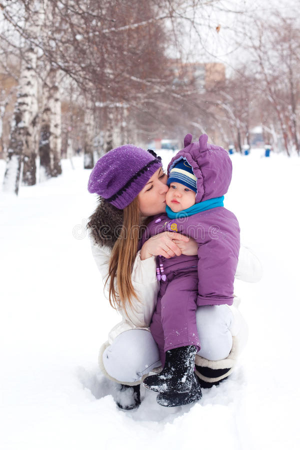 Mother kissing and holding a baby, winter