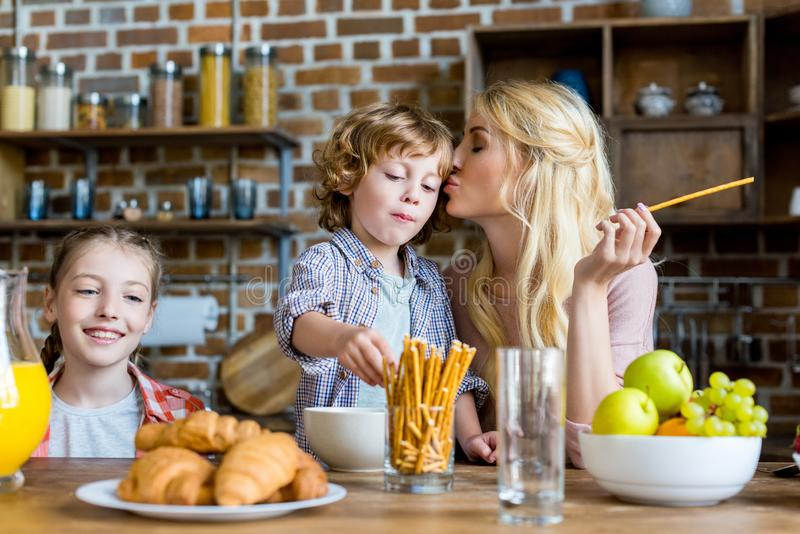 mother kissing son while having breakfast with kids stock photography