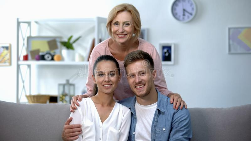 Mother-in-law embracing son and his wife, happy family relationship concept stock image
