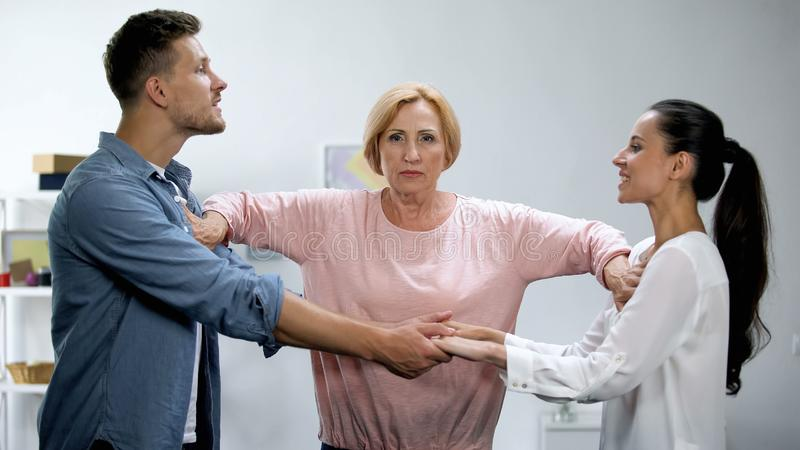 Mother-in-law pushing young man and woman holding hands, interference in family. Mother-in-law pushing young men and women holding hands, interference in family royalty free stock photos