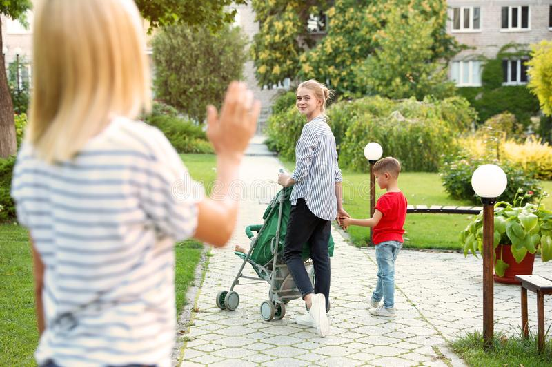 Mother leaving children with teen nanny in. Park stock image