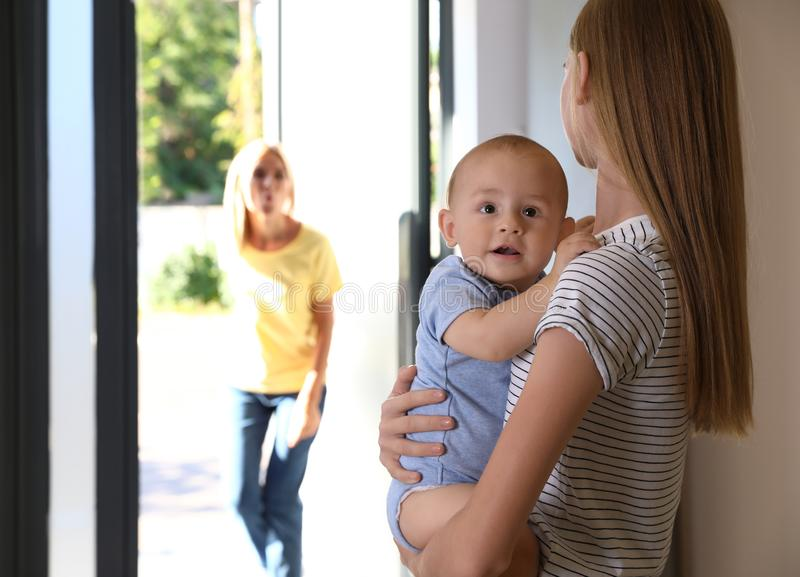 Mother leaving her baby with teen nanny at home stock images